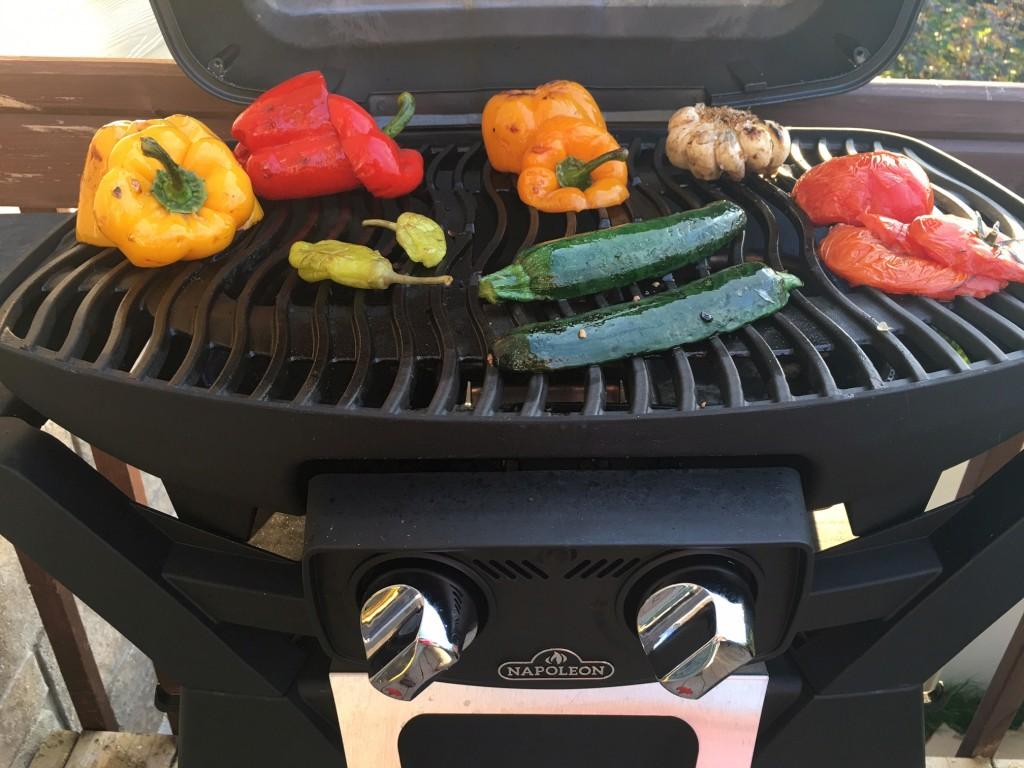 Légumes (poivron, ail, tomates, courgettes) sur un barbecue Napoléon