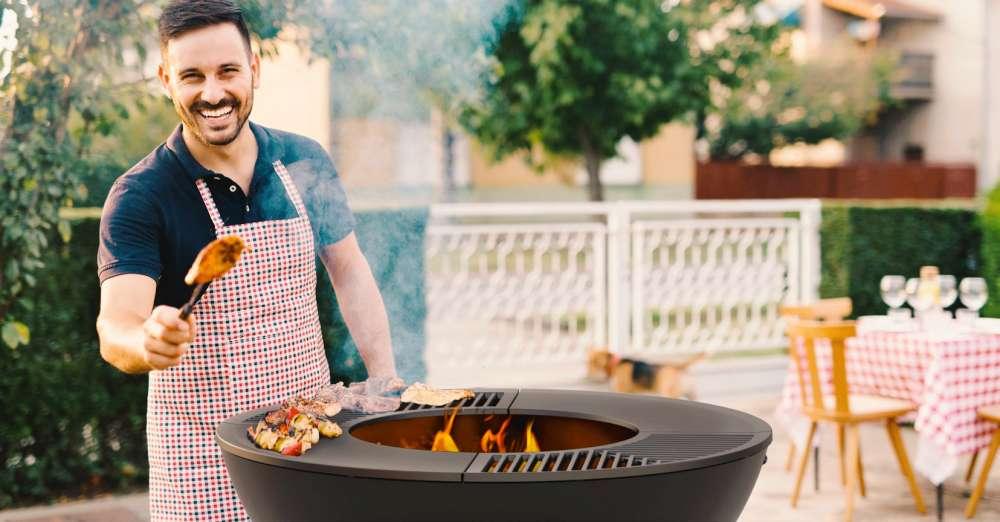 Homme avec tablier cuisine sur un BBQ, gril. Comment tenir le meilleur BBQ de distanciation sociale de l'été!