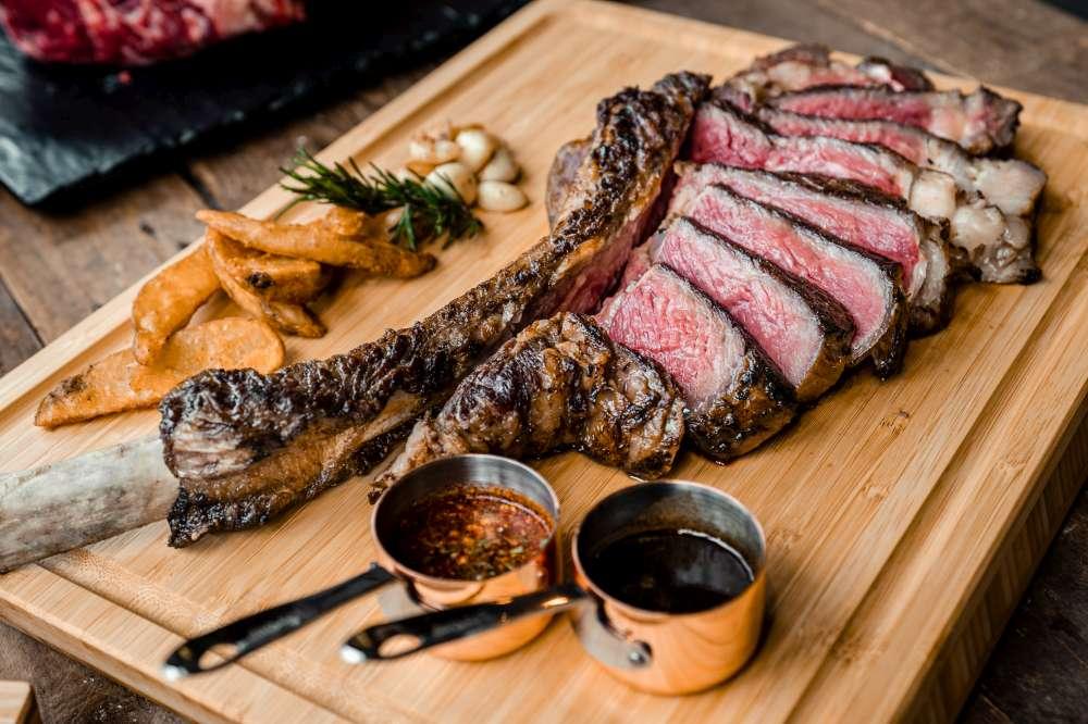 Délicieux steak Tomahawk en tranches sur une planche de bois et près à déguster. Comment cuire le parfait steak Tomahawk?