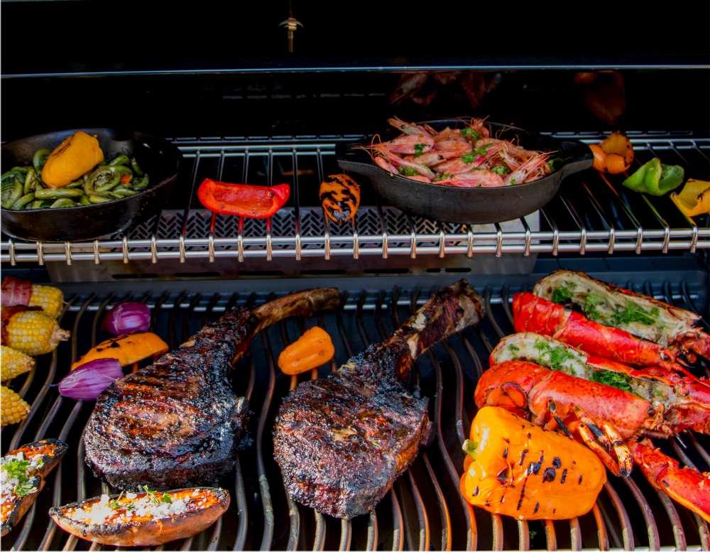 Steak Tomahawk cuit à la perfection sur le BBQ avec des légumes et homards. Comment cuire le parfait steak Tomahawk?